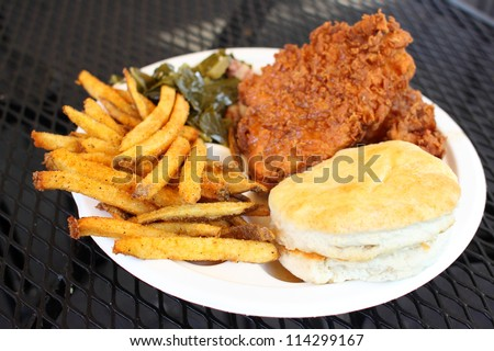 Southern style meal with fried chicken, collard greens with bacon, French fries, and a biscuit.