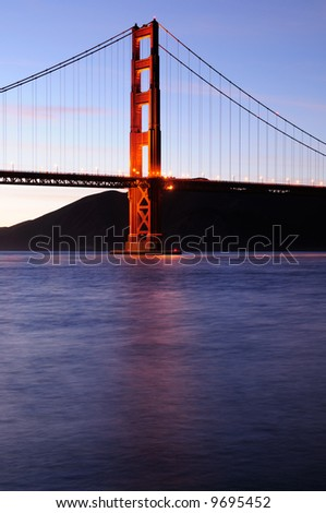 Southern tower of Golden Gate Bridge glows against a background of subtly lit clouds at sunset. Shot from Fort Point area.