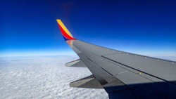 Southwest airplane wing flying above the clouds on a brigh blue sky sunny day.