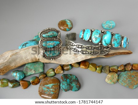 Southwestern jewelry display with large ring, Marc Antia Apache stamped sterling and turquoise cuff and ring all surrounded by many turquoise pieces.
