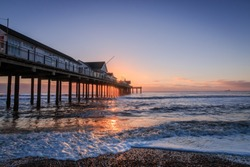Southwold Pier at Sunrise. Taken from the south side of the pier with the rising sun hidden by the pier buildings. Taken at Southwold, Suffolk, UK A beautiful park of the UK. Taken October 2016