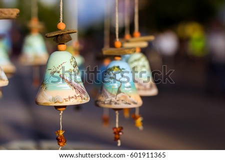 Shutterstock Souvenir decorative bells with image of Palanga bridge, on tongue of bell dangling amber stones. Tourist Souvenirs for memorable shopping. Klaipeda Count, Palanga, Lithuania