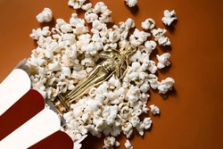 Souvenir golden statuette lies in popcorn on a red background. Film premiere. Rating of the best films. Watch movies. The atmosphere of the cinema.