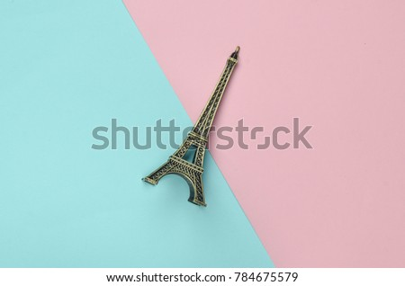 Souvenir statuette of the Eiffel Tower on a multicolored pastel background. Trend of minimalism.