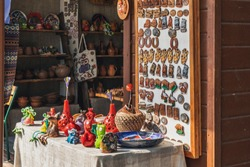 Souvenirs for tourists shopping in souvenir shop near Nesvizh Castle in Nesvizh, Belarus. Handmade clay magnets, toys, vases in memory of the journey