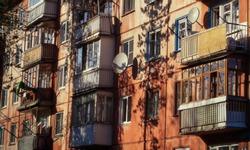 Soviet apartment building. Apartment block. Soviet architecture. Ust-Kamenogorsk (Kazakhstan). Concrete apartment building. Red. Windows and balconies. Closeup detailed fragment