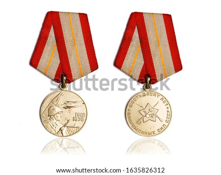 "Soviet commemorative medal ""60 years of the armed forces of the USSR"" on white background. Inscription on the medal is translated: 60 years of the armed forces of the USSR"