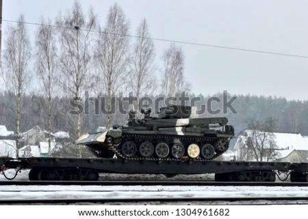 Soviet military armored repair and recovery vehicle on a tracked platform, Belarusian or Russian army. Military battle tanks transported on platforms by rail #1304961682