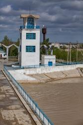 Soviet vintage tower building on Shardara river dam and bridge. Rusted water storage tower right. Yellow river water. Kazaly city, Kyzylorda region, Kazakhstan