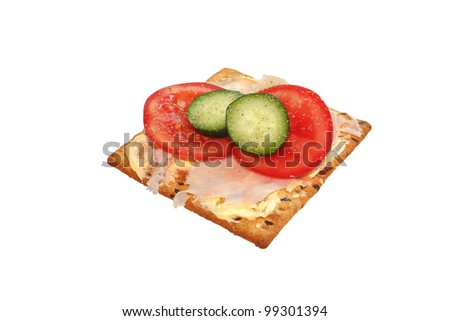 Soy and linseed biscuit with tomato, ham and cucumber topping isolated on a white background using clipping path