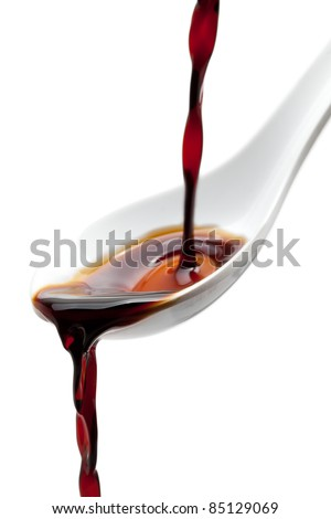 Soy sauce flowing over spoon isolated on white background