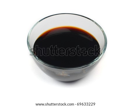 Soy sauce in a transparent plate on a white background