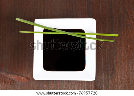 Soy sauce in white square bowl in dark wooden background with chive. Sushi concept.