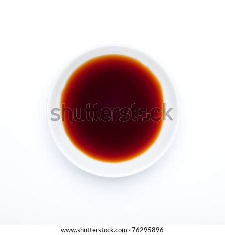 Soy sauce is a condiment produced by fermenting soybeans with a special fungus along with water and salt. Seen from directly above, on a small porcelain plate. / Spice series: Soy sauce