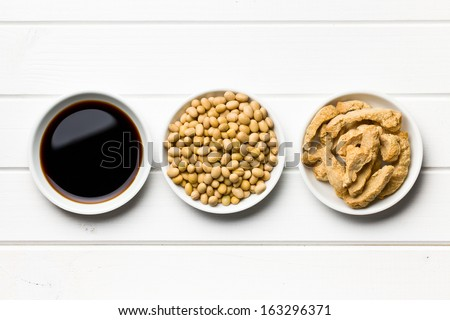 soy sauce, soybeans and soy meat in bowls on wooden table