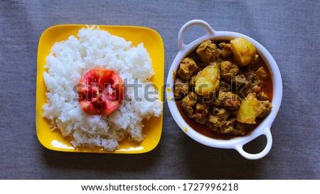 soya chunk well garnished recipe with rice. soya chunk recipe using potato. soya chunk and potato recipe inside white bowl with grey colour background.traditional indian soya chunk recipe