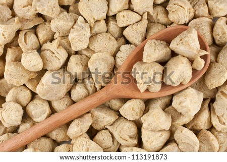 Soya flakes in wooden spoon on soya background