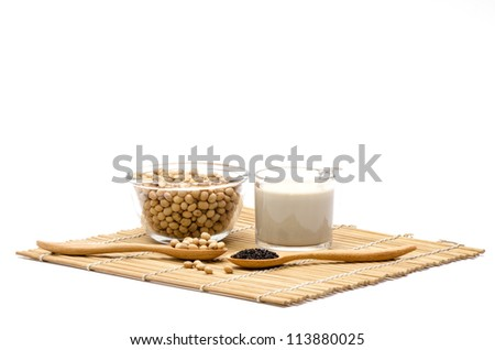 Soya milk and black sesame seeds on a white background. (Glycine max (L.) Merr.).