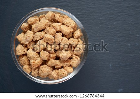 Soybean meat soy meat, meat chunks, chunks in a white bowl on dark background. Copy space. Copy space, place for text.