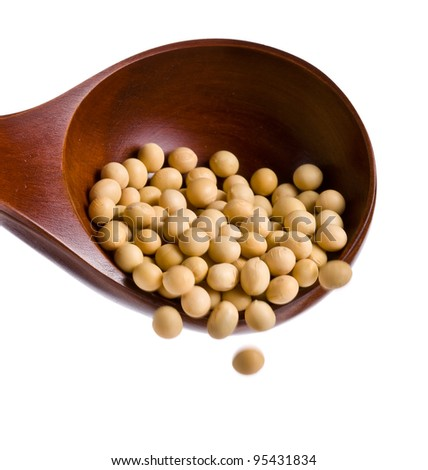 Soybeans falling from a big wooden spoon isolated on white background