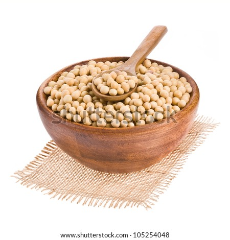 Soybeans on wooden spoon in a wooden bowl isolated on a white background.