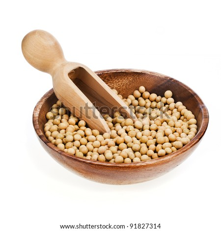 Soybeans on wooden spoon in a wooden bowl on a white background.