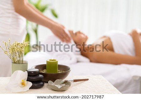 Spa accessories and a woman receiving spa treatment in the background