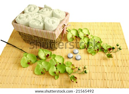 Spa accessories- bamboo mat, therapeutic candles, basket, white towels and orchid flowers