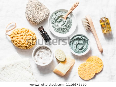 Spa accessories - nut scrub, sponge, facial brush, natural soap, clay face mask, pumice stone, essential oil on a light background, top view. Healthy lifestyle concept. Beauty, skin care. flat lay  Stockfoto ©