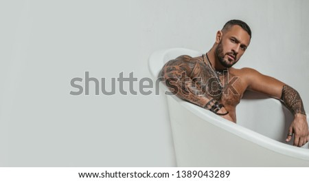 spa and hygiene. time to relax in bathroom. confidence charisma. brutal sportsman. steroids. muscular man with athletic body. sexy abs of tattoo man in bath tub. stay clean and fresh. copy space.