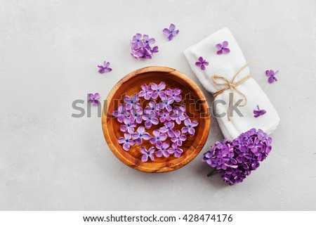 Spa and  wellness composition with perfumed lilac flowers water in wooden bowl and terry towel on gray stone background, aromatherapy, top view, flat lay