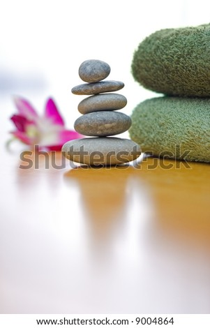Spa and wellness: green towels and a stack of zen pebbles