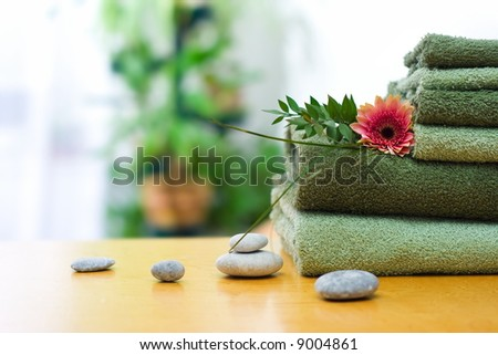Spa and wellness: green towels in bathroom; stones and gerbera decoration