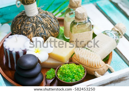 Spa and wellness massage setting. Still life with candle, towel and stones. Outdoor summer background. #582453250