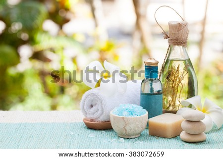 Spa and wellness massage setting Still life with essential oil, salt and stones Outdoor summer background Copy space