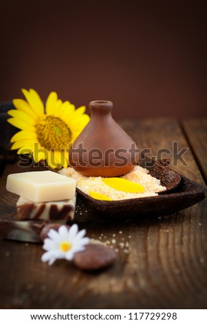 Spa and wellness setting with natural bath salt, candles and towel, massager and sunflower.. Brown dayspa nature set with copyspace - stock photo