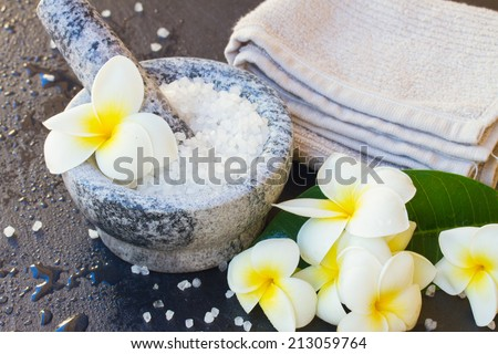 Spa and wellness setting with natural sea sat,  towels  and  frangipani  flowers