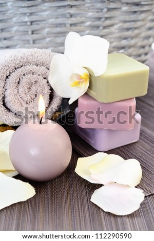 Spa and wellness setting with natural soap, candles and towel. Beige dayspa