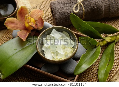 Spa aroma bowl of salt and orchid with towel and green leaves on mat