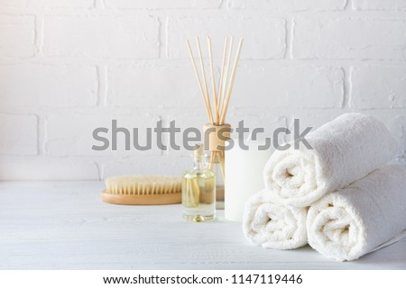 SPA aromatherapy background.  Still life with white towel, bath oil, massage brush and candle. #1147119446