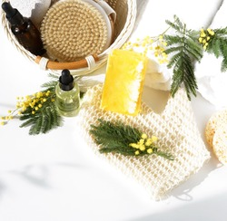 Spa  background. bath products zero waste , sea salt, towels, aroma oil in bottles, natur soap, mimosa flowers, shadows on white backdrop. Beauty, wellness, body care concept. top view. copy space
