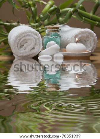 Spa background with bamboo plants, towels, candles and bath salts in green reflected on water.