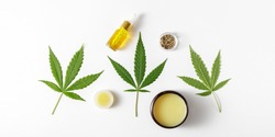 Spa background with CBD oil, cannabis wax salve, leaves and hemp seeds. Light backdrop with copy space