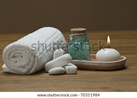 Spa background with  towels, candles and bath salts in green.