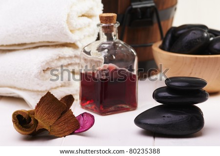 spa, balanced black stones, essential oil and towel on a white table