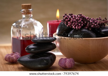 spa, balanced stones, a bowl with black stones and potpourri, bottle with essential oil and candle