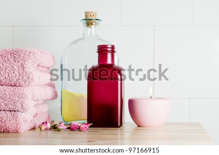 Spa bath items in pink and yellow theme on a light wooden surface against a white tiled wall which provides copy space to the upper right