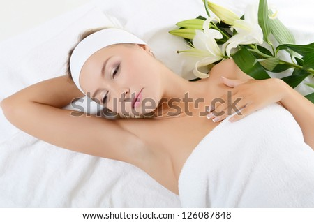 Spa beautiful woman lays with white lily