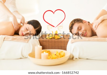 spa, beauty, love and happiness concept - smiling couple with candles, flowers and champagne glasses getting massage in spa salon #166852742