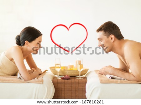 spa beauty love and happiness concept smiling couple with candles in spa salon drinking champagne